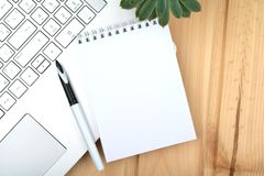 Notepad, laptop, pen, plant on wooden surface. stock photo