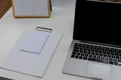 Notepad and laptop on white wooden desk. View from above with copy space in white tone. Work environment and office background royalty free stock image
