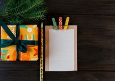 Notepad lays on the wooden background to make a list to do things or list of presents for friends and family. New year royalty free stock image