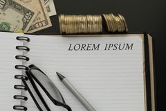 Notepad with Lorem ipsum words, pencil, glasses. And dollar banknotes, stacks of coins on the background royalty free stock image