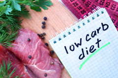 Notepad with low carb diet and fresh meat. On wooden board royalty free stock photos