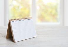 Notepad lub kalendarz na drewnianym stole nad zamazanym nadokiennym tłem Fotografia Royalty Free