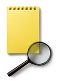 Notepad and magnifying glass Stock Photography