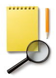 Notepad and magnifying glass Stock Image
