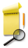 Notepad and magnifying glass Stock Photos