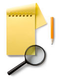 Notepad and magnifying glass Royalty Free Stock Image