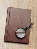 Notepad and magnifying glass Royalty Free Stock Photos