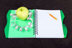 Notepad with measuring tape. And Apple on a black background Stock Image