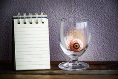 Notepad med ögonbollen i exponeringsglas på trä- och väggbakgrund Genom att använda tapeten eller bakgrund för den halloween dage Fotografering för Bildbyråer