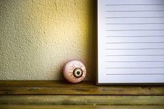 Notepad med ögonbollen i exponeringsglas på trä- och väggbakgrund Genom att använda tapeten eller bakgrund för den halloween dage Arkivbild