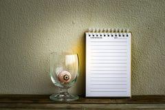 Notepad med ögonbollen i exponeringsglas på trä- och väggbakgrund Genom att använda tapeten eller bakgrund för den halloween dage Arkivbilder