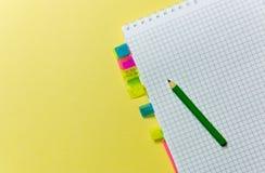 Notepad med bokmärker, blyertspenna för att anteckna på gul bakgrund kontorsproblemläge som löser tema fotografering för bildbyråer