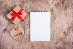Notepad med den tomma sidan, en överraskning och en trähjärta Notepad med tomma sidor och ett överraskningvalentinträ kopiera avs Royaltyfri Foto