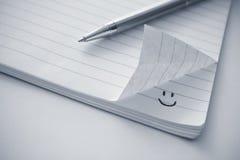 Notepad med en smileysymbol Arkivbild