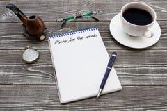 Notepad med inskriften, penna: `-Plan för veckan: ` med en kopp kaffe, ett rör, exponeringsglas och en rova arkivfoto