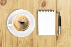 Notepad med kaffe på skrivbordet royaltyfri fotografi