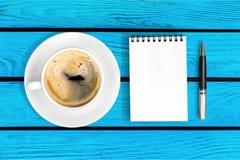 Notepad med kaffe på skrivbordet arkivbilder