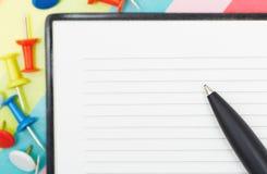 Notepad med pennan och häftstift royaltyfri foto