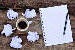 Notepad med pennkaffe och skrynkligt papper på skrivbordet arkivbild