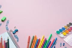 Notepad med stationära objekt på rosa bakgrund St?lle f?r din text royaltyfri fotografi