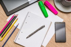 Notepad, mobile phone, paper, pencils and tablet on table Royalty Free Stock Images