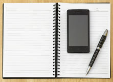 Notepad with mobile phone. Notepad on a table with mobile phone Royalty Free Stock Images