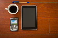 Notepad, mobile phone, tablet and coffee cup as seen from above sitting on wooden surface.  stock images