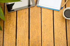 Notepad, mobile phone, tablet and coffee cup as seen from above sitting on wooden surface.  royalty free stock images
