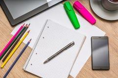 Notepad, mobiltelefon, papper, blyertspennor och minnestavla på tabellen Royaltyfria Bilder