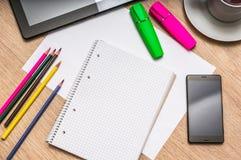Notepad, mobiltelefon, papper, blyertspennor och minnestavla på tabellen Fotografering för Bildbyråer