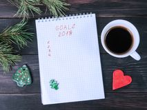 Notepad with notes, coffee mug and Christmas tree decorations on a dark table Stock Photo