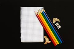 Notepad for notes and color pencils on black background. Top view Royalty Free Stock Photography