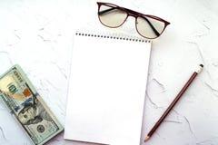 Notepad, ołówek, szkła i my, dolary na lekkim tle zdjęcia royalty free