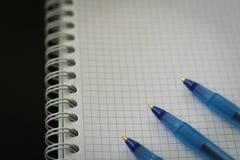 Notepad obciosywał z błękitnymi piórami na czarnym tle dla edukaci, biznes z kopii przestrzenią Fotografia Stock