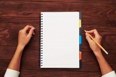 Notepad och blyertspenna i kvinnas hand Arkivfoton