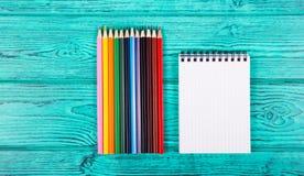 Notepad och färgade blyertspennor på en blå bakgrund Brevpapper på tabellen Royaltyfri Foto