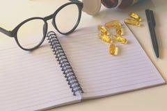 Notepad- och för omega 3 kapsel Arkivfoto