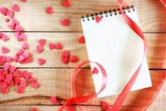 Notepad och godis i formen av hjärta Arkivfoto