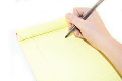 Notepad och hand med en penna på en vit bakgrund Royaltyfri Fotografi