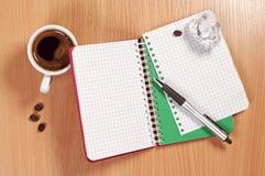Notepad och kaffe på skrivbordet arkivbild