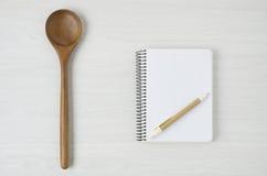 Notepad och träsked på den vita wood tabellen arkivfoto