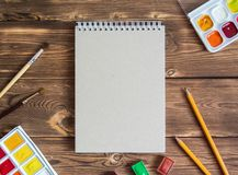 Notepad with office supplies on a wooden brown background royalty free stock photos