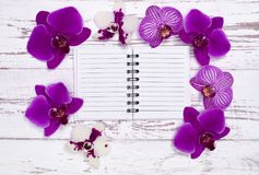 Notepad on old wooden table decorated with flowers Stock Image