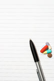 Notepad, one pen, pills. Empty blank ring, notepad, one black pen on white page with pills to indicate relation with pharmaceutical industry, or metaphor for Royalty Free Stock Photo