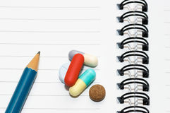 Notepad, one pencil, pills. Empty blank ring, notepad, one pencil on white page with pills to indicate relation with pharmaceutical industry, or metaphor for Stock Image