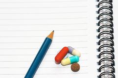 Notepad, one pencil, pills. Empty blank ring, notepad, one pencil on white page with pills to indicate relation with pharmaceutical industry, or metaphor for royalty free stock photo