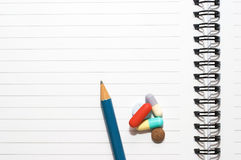 Notepad, one pencil, pills. Empty blank ring, notepad, one pencil on white page with pills to indicate relation with pharmaceutical industry, or metaphor for Stock Photography