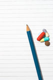 Notepad, one pencil, pills. Empty blank ring, notepad, one pencil on white page with pills to indicate relation with pharmaceutical industry, or metaphor for royalty free stock image