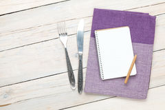 Notepad over kitchen towel and silverware on wooden table Stock Images