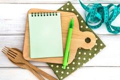 Notepad på skärbräda med den trägaffeln och skeden och mig Arkivfoto